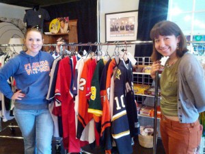 Former UF veterinary student Meredith Montgomery, left, a 2015 graduate of the college, poses with a volunteer near a rack full of sports jerseys that were among the items auctioned off May 2, 2014 at Cymplify to benefit UF's HAARTS program. The event was put on by the college's Shelter Medicine Club.