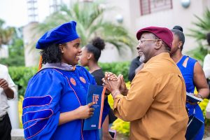 Shonte Bishop, D.V.M., a new graduate from the Class of 2018, shares a special moment with her father after college commencement exercises on May 26.